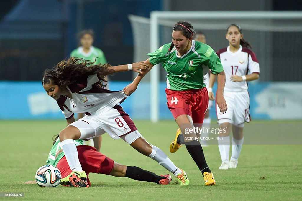 Nathalie Pasquel of Venezuela battles with Kimberly Rodriguez of Mexico during the 2014 FIFA Girls Summer Youth Olympic Football Tournament Semi Final match between Venezuela and Mexico at Wutaishan Stadium on August 23, 2014 in Nanjing, China.