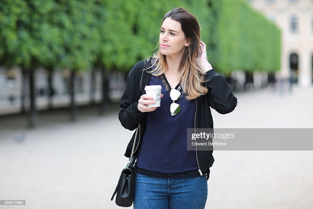 Nathalie Van den Berg (fashion blogger - Curls and bags), is holding a Cafe Kitsune coffee cup, and is wearing a Frnch blue top, a Zara black bomber jacket, a Love Moschino black bag, and Dior sunglasses, during a street style session, at the Jardins du Palais Royal, in the 1st quarter of Paris, on May 24, 2016 in Paris.