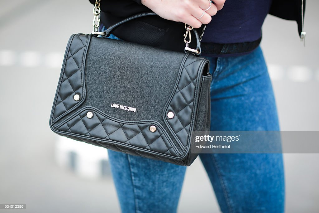 Nathalie Van den Berg (fashion blogger - Curls and bags), is wearing a Frnch blue top, a Zara black bomber jacket, Senso white shoes, a Love Moschino black bag, and Dior sunglasses, during a street style session, at the Colonnes de Buren (Les Deux Plateaux - Palais Royal), in the 1st quarter of Paris, on May 24, 2016 in Paris.