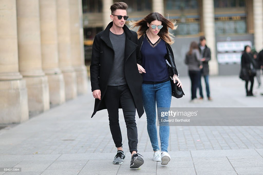 Nathalie Van den Berg (R) (fashion blogger - Curls and bags), is wearing a Frnch blue top, a Zara black bomber jacket, Senso white shoes, a Love Moschino black bag, and Dior sunglasses. Jeroen Van Es (L), is wearing gray Adidas Originals shoes, Diesel black pants, an All Saints gray shirt, an All Saints black coat, Rayban sunglasses, and a Daniel Wellington watch, during a street style session, at Palais Royal, in the 1st quarter of Paris, on May 24, 2016 in Paris.