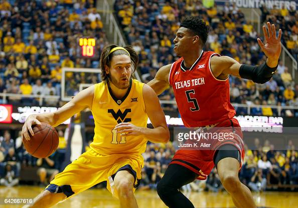 Nathan Adrian of the West Virginia Mountaineers handles the ball against Justin Gray of the Texas Tech Red Raiders at the WVU Coliseum on February 18...