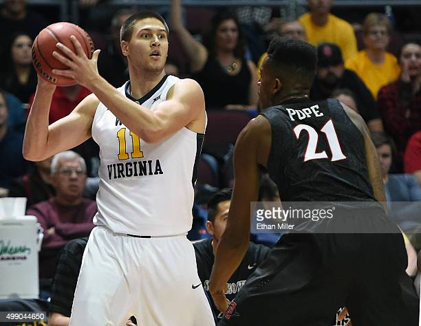 Nathan Adrian of the West Virginia Mountaineers is guarded by Malik Pope of the San Diego State Aztecs during the championship game of the 2015...