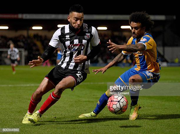 Nathan Arnold oif Grimsby is challenged by Junior Brown of Shrewsbury during the Emirates FA Cup second round match between Grimsby Town and...