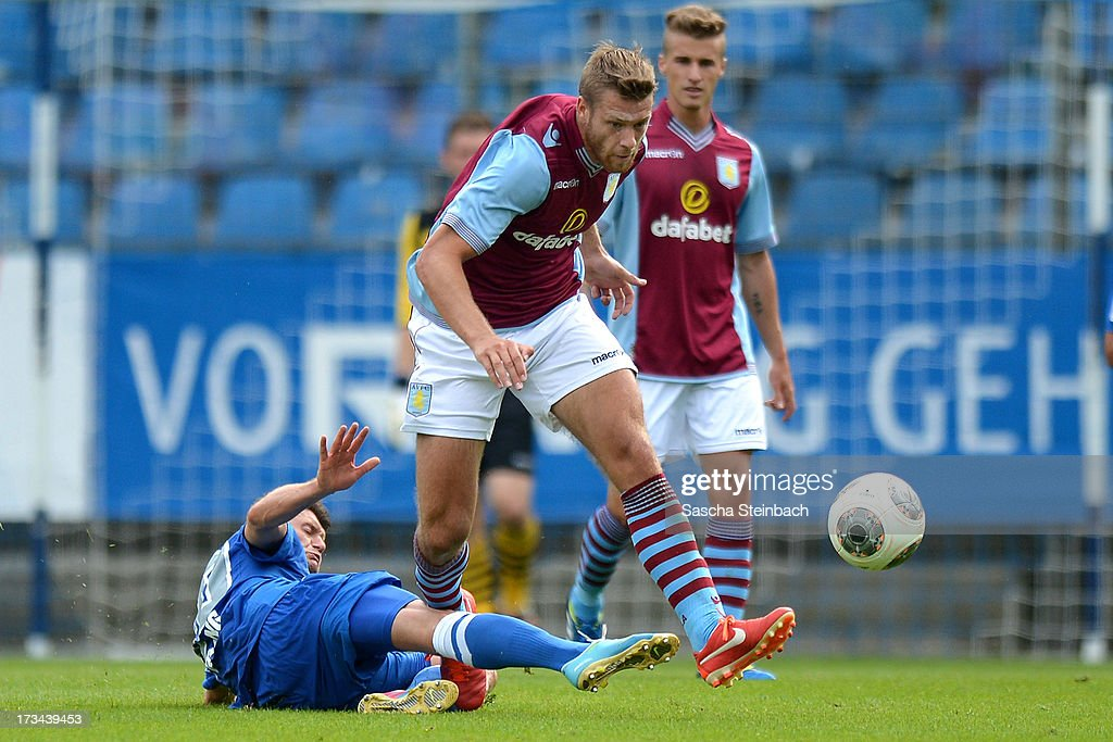 Nathan Baker (R) of Aston Villa is tackled by Piotr Cwielong (L) of Bochum during the pre-season friendly match between VfL Bochum and Aston Villa at Rewirpower Stadium on July 14, 2013 in Bochum, Germany.