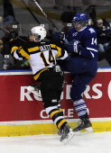 Nathan Bastian of the Mississauga Steelheads takes a hit from Loren Ulett of the Kingston Frontenacs during game action on March 16 2014 at the...
