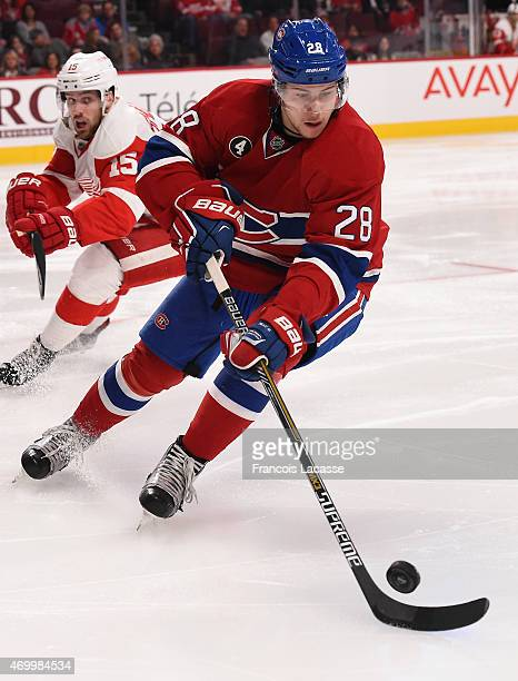 Nathan Beaulieu of the Montreal Canadiens controls the puck while being challenged by Riley Sheahan of the Detroit Red Wings in the NHL game at the...