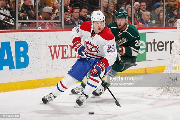 Nathan Beaulieu of the Montreal Canadiens handles the puck with Thomas Vanek of the Minnesota Wild defending during the game on December 22 2015 at...