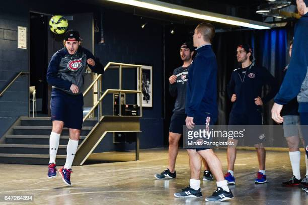 Nathan Beaulieu of the Montreal Canadiens plays soccer while teammates look on prior to the NHL game against the Nashville Predators at the Bell...