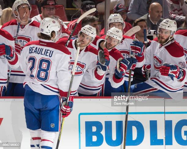 Nathan Beaulieu of the Montreal Canadiens pounds gloves with teammates on the bench following his second period goal during an NHL game against the...