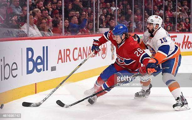 Nathan Beaulieu of the Montreal Canadiens skates for the puck while being challenged by Cal Clutterbuck of the New York Islanders in the NHL game at...