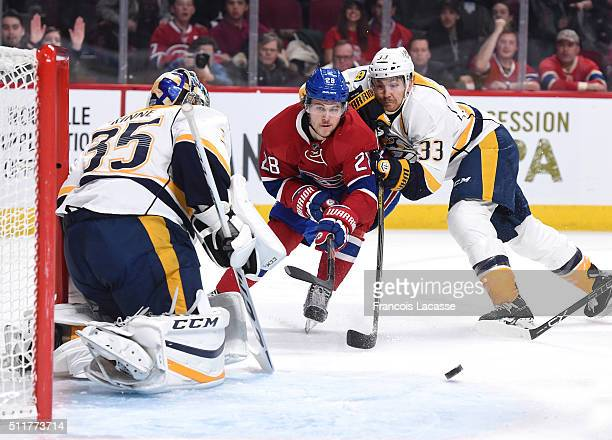 Nathan Beaulieu of the Montreal Canadiens tries to keep the puck from Colin Wilson of the Nashville Predators in the NHL game at the Bell Centre on...