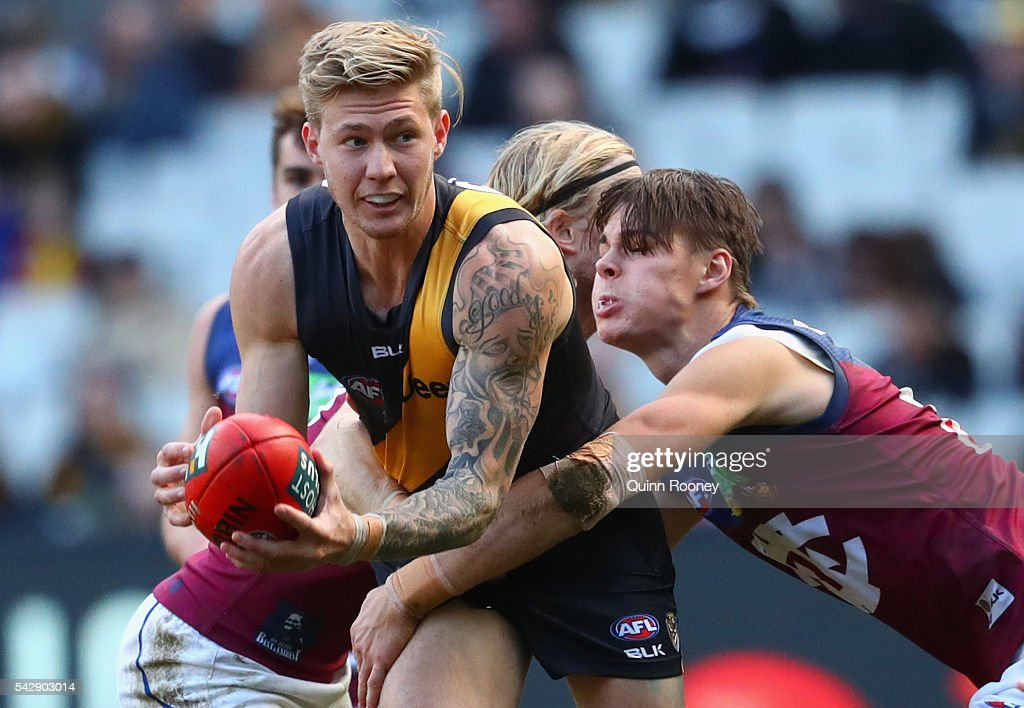 Nathan Broad of the Tigers handballs whilst being tackled by Eric Hipwood of the Lions during the round 14 AFL match between the Richmond Tigers and the Brisbane Lions at Melbourne Cricket Ground on June 25, 2016 in Melbourne, Australia.