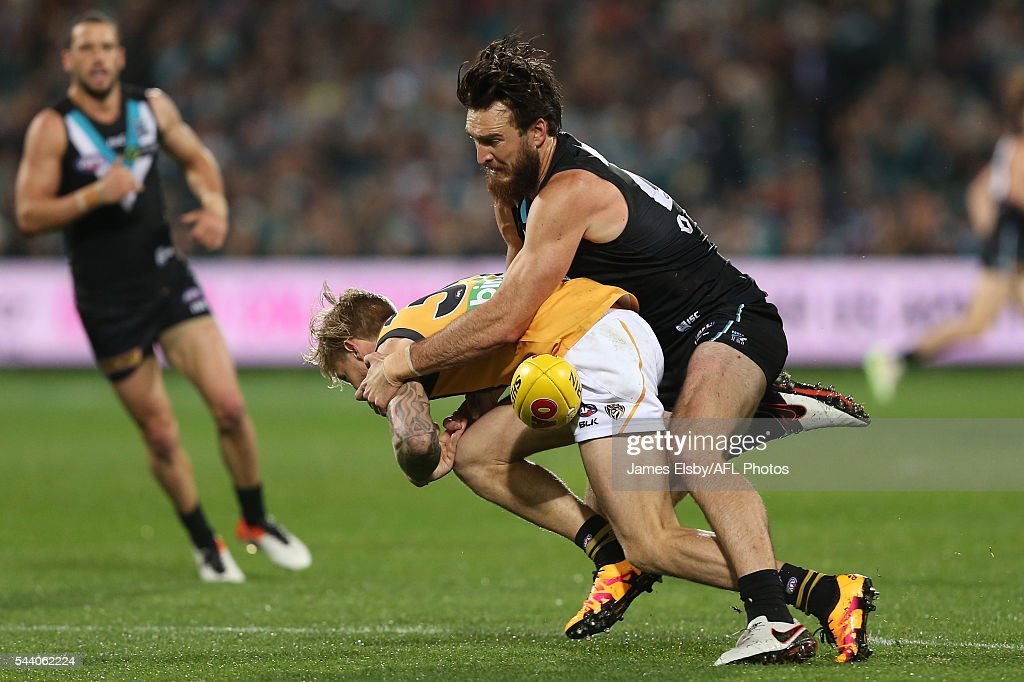 Nathan Broad of the Tigers is tackled by Charlie Dixon of the Power during the 2016 AFL Round 15 match between Port Adelaide Power and the Richmond Tigers at Adelaide Oval on July 1, 2016 in Adelaide, Australia.