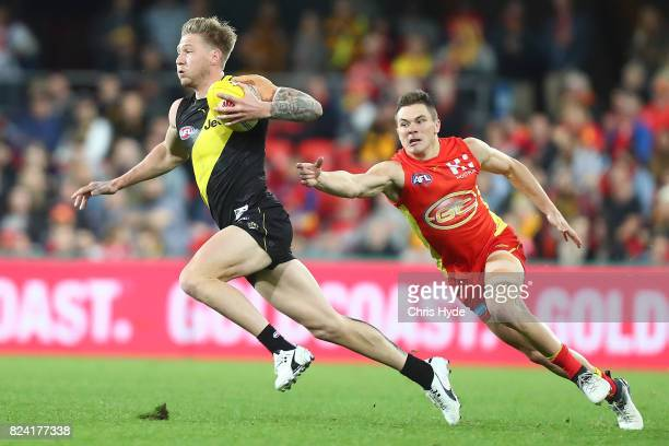 Nathan Broad of the Tigers runs the ball during the round 19 AFL match between the Gold Coast Suns and the Richmond Tigers at Metricon Stadium on...