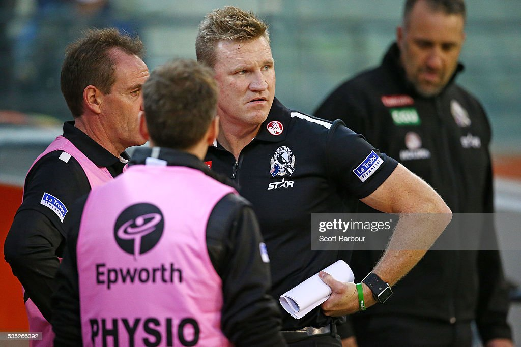 Nathan Buckley, coach of the Magpies speaks to his medical team at three quarter time during the round 10 AFL match between the Collingwood Magpies and the Western Bulldogs at Melbourne Cricket Ground on May 29, 2016 in Melbourne, Australia.