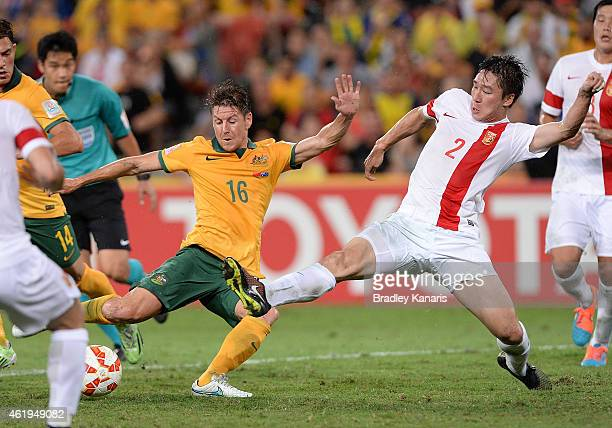 Nathan Burns of Australia attempts to get a kick away as he is pressured by the defence of Ren Hang of China during the 2015 Asian Cup match between...
