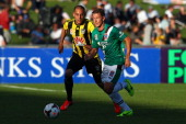 Nathan Burns of the Jets runs the ball under pressure from Leo Bertos of the Phoenix during the round three ALeague match between Wellington Phoenix...