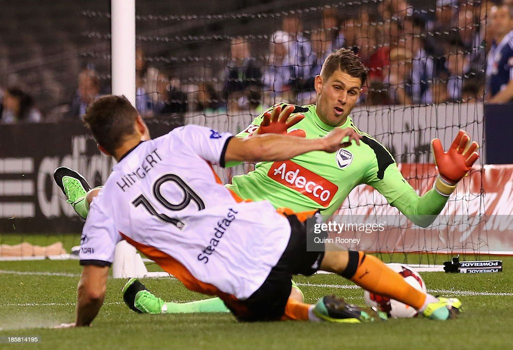 Nathan Coe of the Victory stops a shot on goal by Jack Hingert of the Roar during the round three A-League match between Melbourne Victory and Brisbane Roar at Etihad Stadium on October 25, 2013 in Melbourne, Australia.
