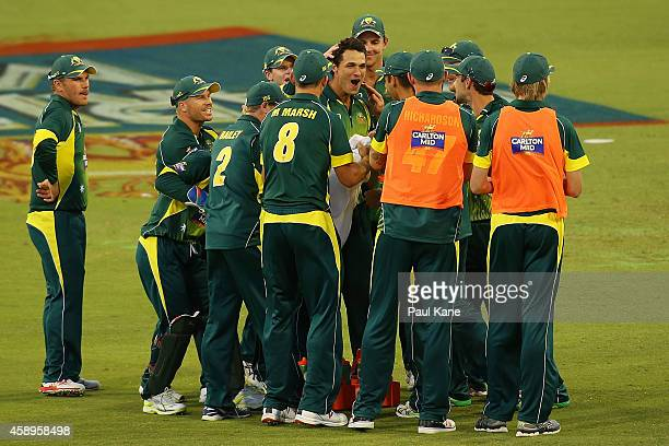 Nathan CoulterNile of Australia reacts with team mates after the DRS replay is shown on the big screen for the dismissal of Ryan McLaren of South...