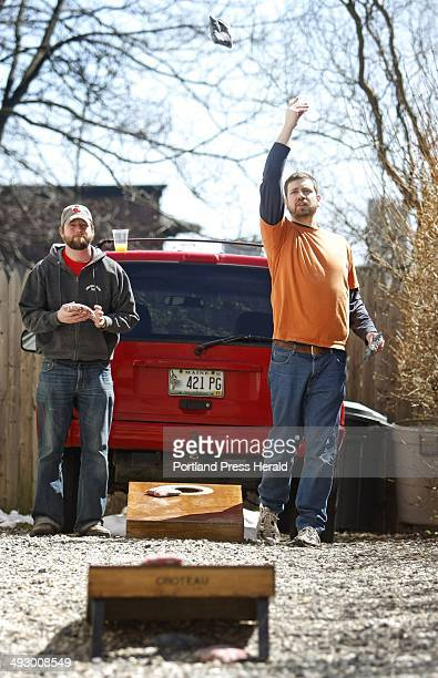 Nathan Croteau of Portland left and Bryan O'Connor of South Portland toss bags filled with corn into platforms with holes in a game of 'Bags'...