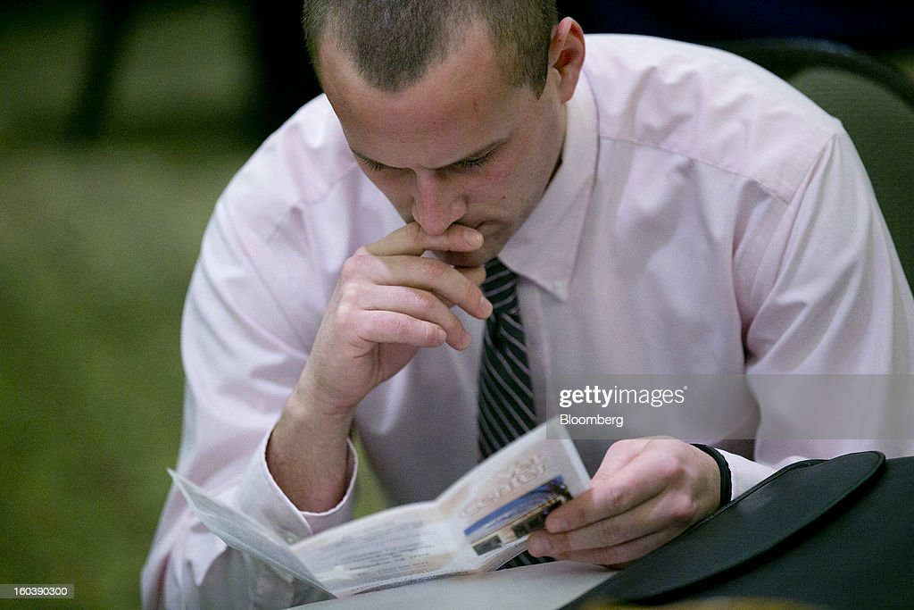Nathan DeSantis looks at a company brochure at a National Career Fairs job fair in Arlington, Virginia, U.S., on Wednesday, Jan. 30, 2013. The U.S. Labor Department is scheduled to release initial jobless claims data on Jan. 31. Photographer: Andrew Harrer/Bloomberg via Getty Images