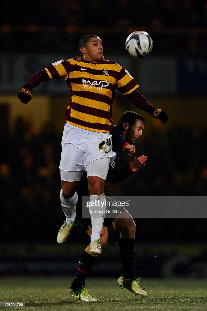 Nathan Doyle of Bradford rises above Jack Wilshere of Arsenal to win a header during the Capital One Cup quarter final match between Bradford City and Arsenal at the Coral Windows Stadium, Valley Parade on December 11, 2012 in Bradford, England.