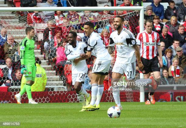 Nathan Dyer of Swansea City celebrates with teammates Neil Taylor and Kyle Bartley after scoring the opening goal during the Barclays Premier League...