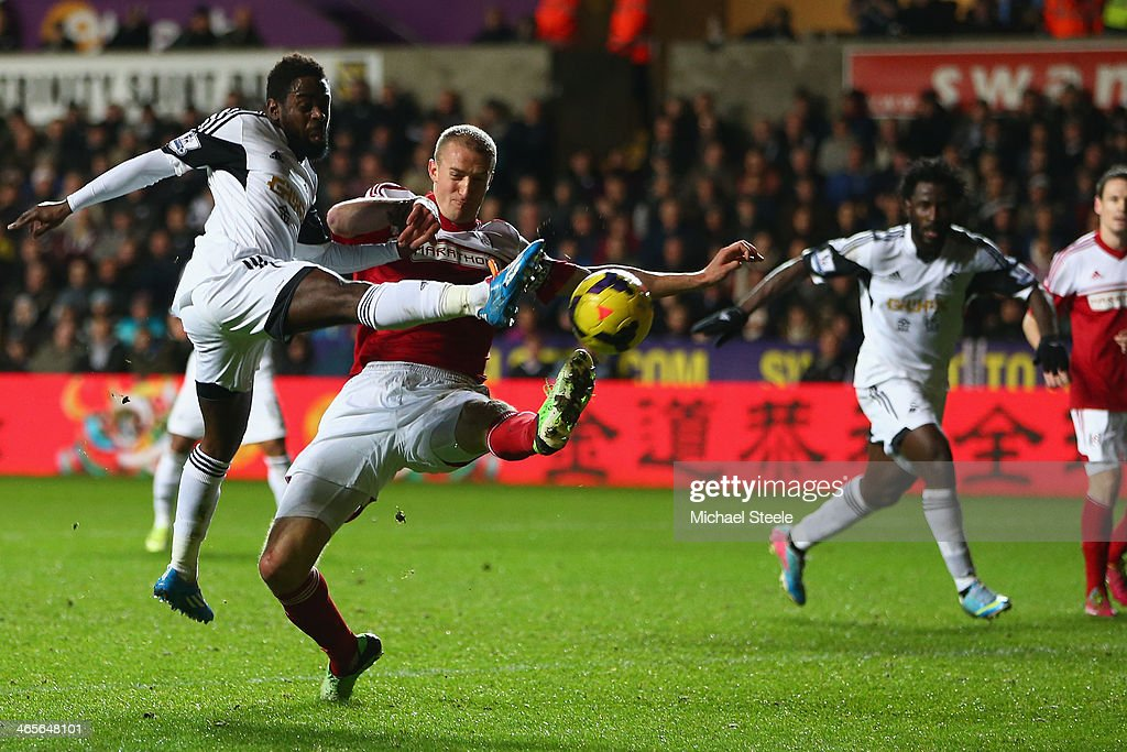 Nathan Dyer (L)of Swansea City shoots despite the attentions of <a gi-track='captionPersonalityLinkClicked' href=/galleries/search?phrase=Brede+Hangeland&family=editorial&specificpeople=618174 ng-click='$event.stopPropagation()'>Brede Hangeland</a> of Fulham during the Barclays Premier League match between Swansea City and Fulham at the Liberty Stadium on January 28, 2014 in Swansea, Wales.