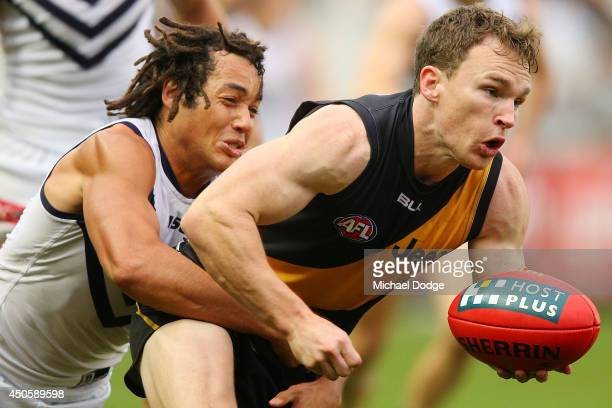 Nathan Foley of the Tigers is tacked by Tendai Mzungu of the Dockers during the round 13 AFL match between the Richmond Tigers and the Fremantle...