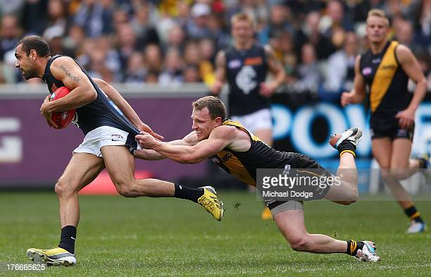 Nathan Foley of the Tigers tackles Chris Yarran of the Blues during the round 21 AFL match between the Richmond Tigers and the Carlton Blues at...