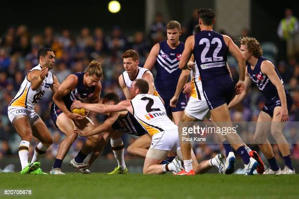 Nathan Fyfe of the Dockers contests for the ball against Shaun Burgoyne and Jarryd Roughead of the Hawks during the round 18 AFL match between the...