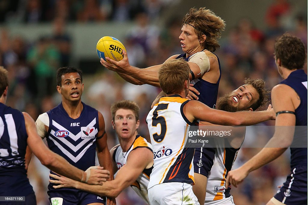 Nathan Fyfe of the Dockers looks to handball while being tackled by Will Schofield of the Eagles during the round one AFL match between the Fremantle Dockers and the West Coast Eagles at Patersons Stadium on March 23, 2013 in Perth, Australia.