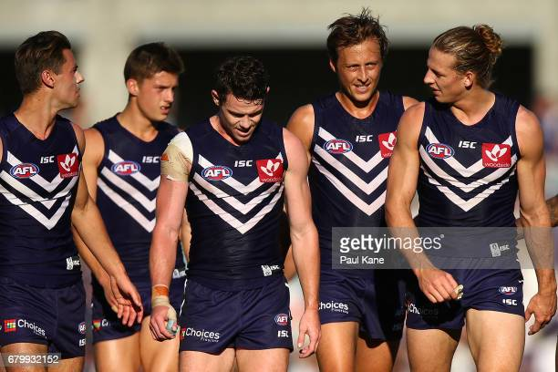 Nathan Fyfe of the Dockers talks with Cameron Sutcliffe Lachie Neale and Lachie Weller while walking from the field at the half time break during the...