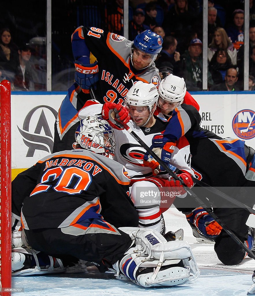 Nathan Gerbe #14 and Patrick Dwyer #39 of the Carolina Hurricanes crash the crease against Evgeni Nabokov #20 of the New York Islanders at the Nassau Veterans Memorial Coliseum on January 4, 2014 in Uniondale, New York. The Hurricanes defeated the Islanders 3-2.
