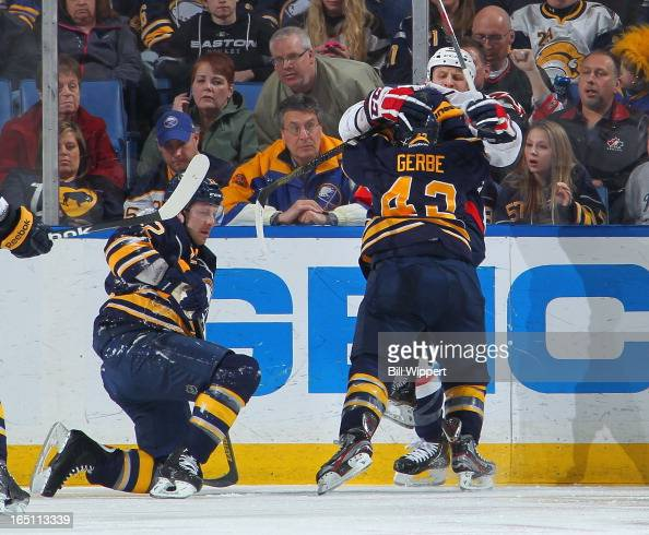 Nathan Gerbe of the Buffalo Sabres challenges Steve Oleksy of the Washington Capitals after teammate Kevin Porter was checked by Oleksy on March 30...