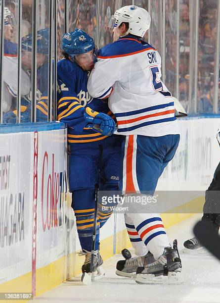 Nathan Gerbe of the Buffalo Sabres gets checked into the boards by Ladislav Smid of the Edmonton Oilers at First Niagara Center on January 3 2012 in...