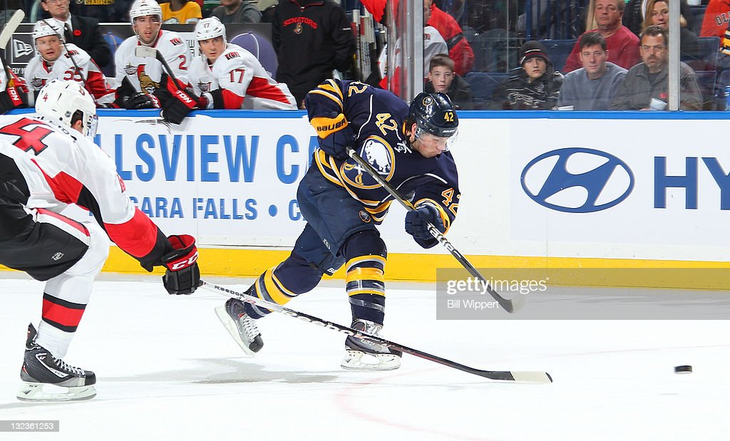<a gi-track='captionPersonalityLinkClicked' href=/galleries/search?phrase=Nathan+Gerbe&family=editorial&specificpeople=697084 ng-click='$event.stopPropagation()'>Nathan Gerbe</a> #42 of the Buffalo Sabres takes a slapshot against Chris Phillips #4 of the Ottawa Senators at First Niagara Center on November 11, 2011 in Buffalo, New York.