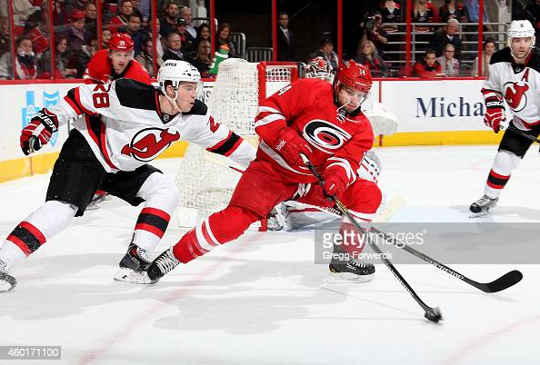 Nathan Gerbe of the Carolina Hurricanes and Damon Severson of the New Jersey Devils battle for the puck near the net during their NHL game at PNC...