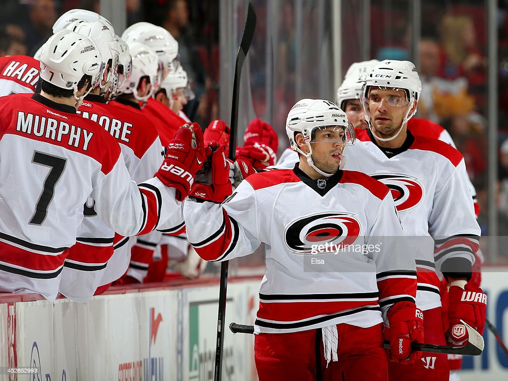 Nathan Gerbe #14 of the Carolina Hurricanes celebrates with teammates on the bench in the first period against the New Jersey Devils at Prudential Center on November 27, 2013 in Newark, New Jersey.