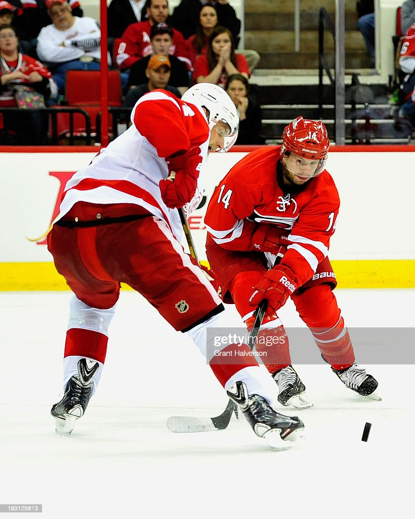 <a gi-track='captionPersonalityLinkClicked' href=/galleries/search?phrase=Nathan+Gerbe&family=editorial&specificpeople=697084 ng-click='$event.stopPropagation()'>Nathan Gerbe</a> #14 of the Carolina Hurricanes slips a pass by Jakub Kindle #4 of the Detroit Red Wings during play at PNC Arena on October 4, 2013 in Raleigh, North Carolina.