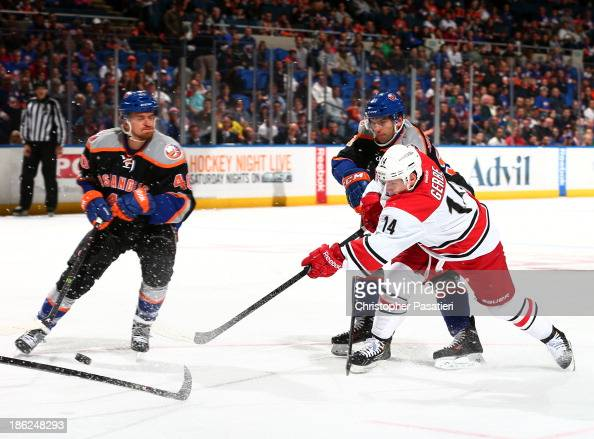 Nathan Gerbe of the Carolina Hurricanes takes a shot on goal against John Tavares and Michael Grabner of the New York Islanders during the first...
