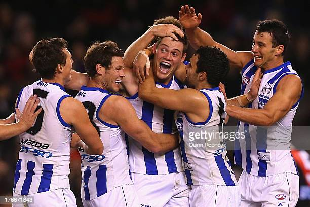 Nathan Grima of the Kangaroos is congratulated by team mates after kicking a goal during the round 21 AFL match between the Essendon Bombers and the...