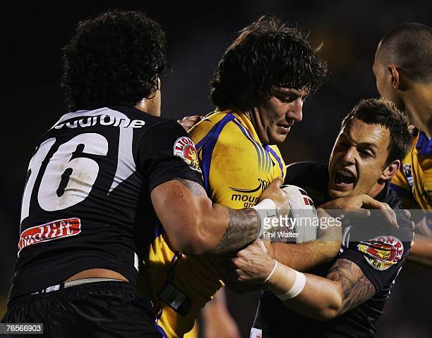 Nathan Hindmarsh of the Parramatta Eels is tackled by Epalahame Lauaki and Nathan Fien of the Warriors during the NRL qualifying final match between...