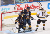 Nathan Horton of the Boston Bruins scores Boston's second goal against Andrej Sekera and Ryan Miller of the Buffalo Sabres at First Niagara Center on...