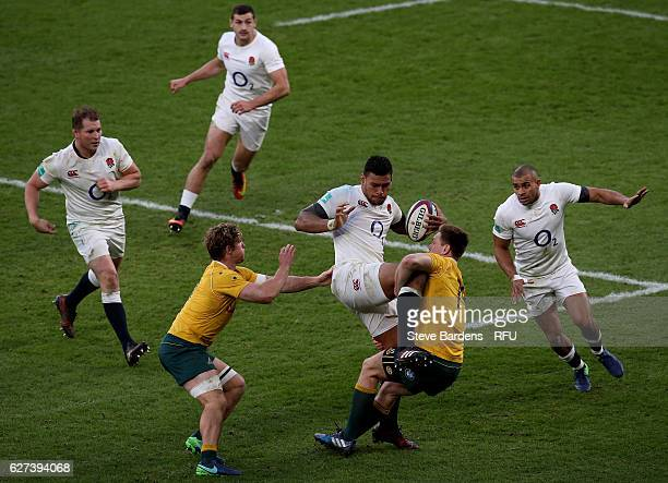 Nathan Hughes of England is tackled by Michael Hooper and Dane HaylettPetty of Australia during the Old Mutual Wealth Series match between England...