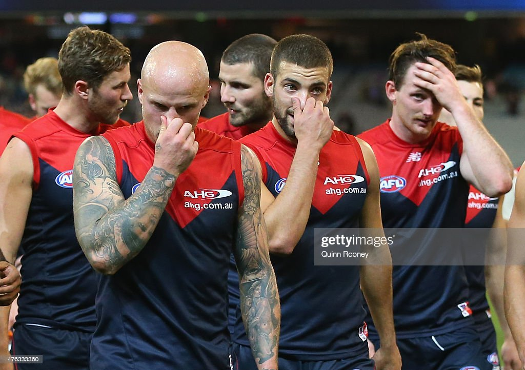 Nathan Jones Jimmy Toumpas and Aidan Riley of the Demons look dejected after losing the round 10 AFL match between the Melbourne Demons and the...