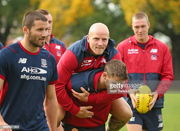 Nathan Jones jumps on the back of his teammates during a Melbourne Demons AFL training session at AAMI Park on May 9 2014 in Melbourne Australia