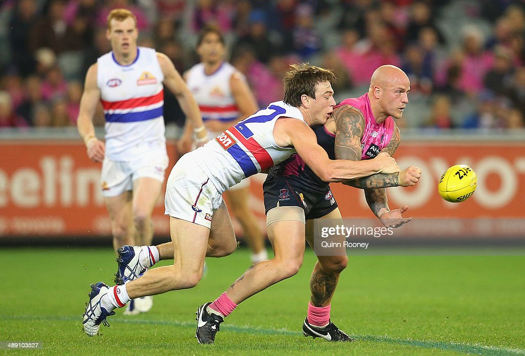 Nathan Jones of the Demons handballs whilst being tackled by Liam Picken of the Bulldogs during the round eight AFL match between the Melbourne...