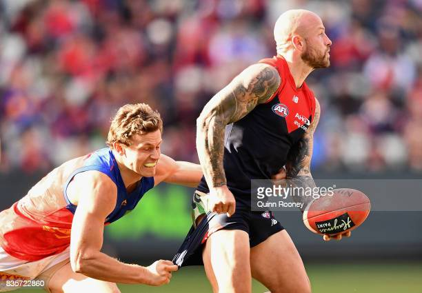 Nathan Jones of the Demons handballs whilst being tackled by Ryan Lester of the Lions during the round 22 AFL match between the Melbourne Demons and...