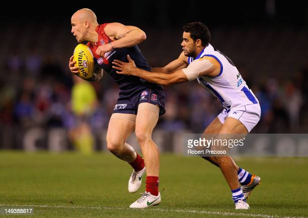 Nathan Jones of the Demons is tackled by Daniel Wells of the Kangaroos during the round 18 AFL match between the North Melbourne Kangaroos and the...